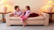 Mother lies on sofa and talk with her daughter sits near