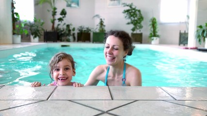 Little girl with her mother stay on edge of indoor pool