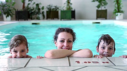 Mother with two kids boy and girl smile at pool edge