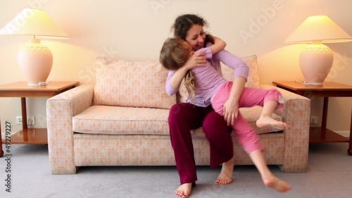 woman sit on sofa and catches her daughter runs to room with