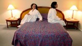 Man with woman in bathrobes come to bedroom and sit on each