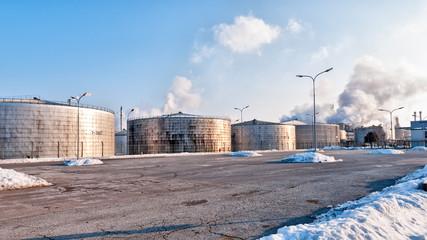Ölraffinerie mit rauchenden Schloten im Hintergrund