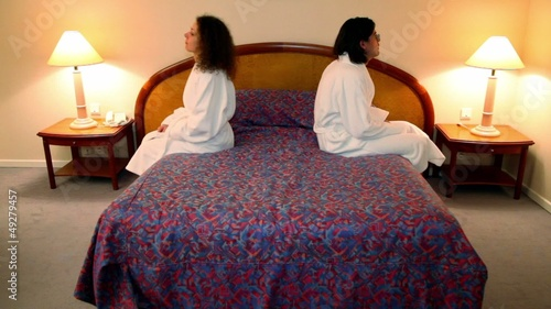 Man with woman in bathrobes come to bedroom, sit on bed and turn