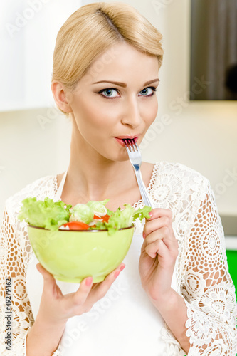 Portrait of a beautiful young woman eating vegetable salad
