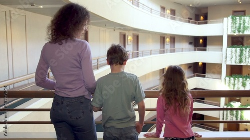 Mother and two her kids stand on balcony in multiple floor