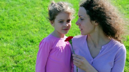 Mother hold red flower and tell about WWII to her little