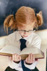 девочка в очках держит в руках книгу