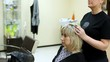 woman sits in hairdressing salon in seat to make hairdress
