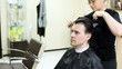 Hairdresser cuts hair to man with long hair by scissors