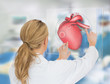 Blonde doctor consulting touchscreen displaying heart diagram
