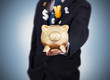 Businessman holding a gold piggy bank