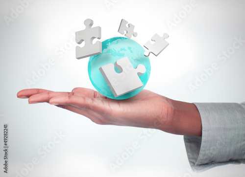 Hand with digital puzzles and a globe