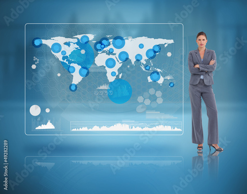 Stern businesswoman standing against a futuristic screen