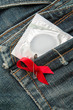 Condom in jeans pocket with red awareness ribbon pinned on