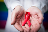 Man holding red aids ribbon