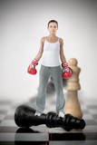 Female boxer standing on black chess piece