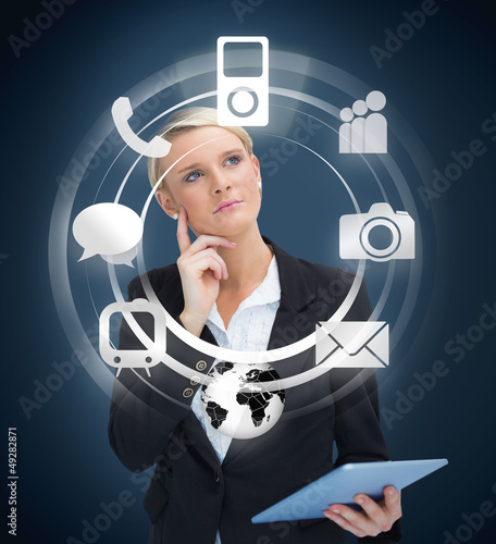 Thoughtful businesswoman with tablet pc considering various appl