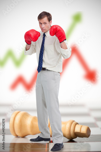 Businessman in boxing gloves on chessboard