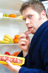 Handsome man eating ham slice near open fridge