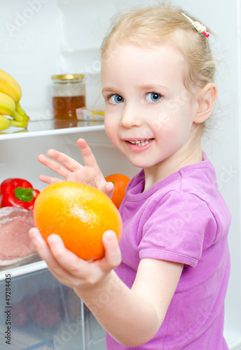 Happy smiling little girl holding orange