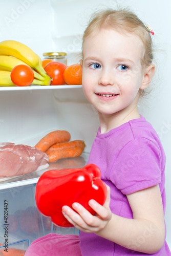 Happy smiling little girl holding paprika