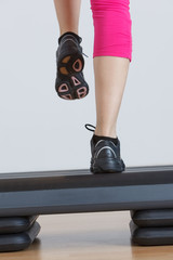 Close up of feet in step equipment at gym