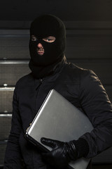 masked hacker holding computer