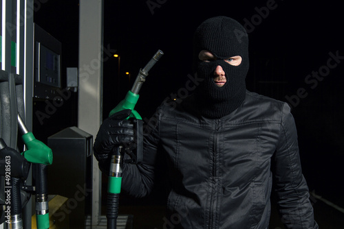 masked man using gas pump