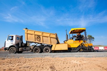 Tipper unloading fresh asphalt from body into tracked paver