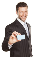 smiling handsome businessman showing a credit card