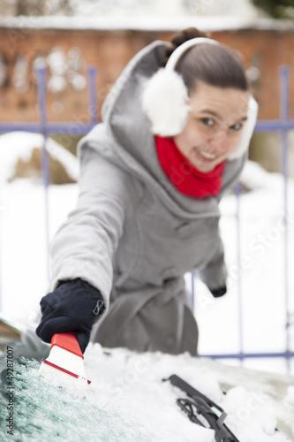 Smiling cute woman removing ice from the car windshield-DOF