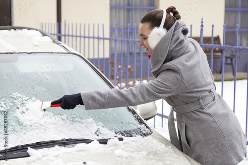 Smiling cute woman removing ice from the car windshield