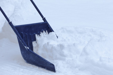 Manual snow removal with snow scoop after blizzard