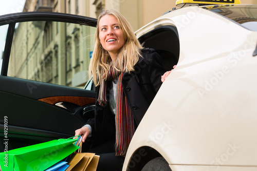 Young woman gets out of taxi