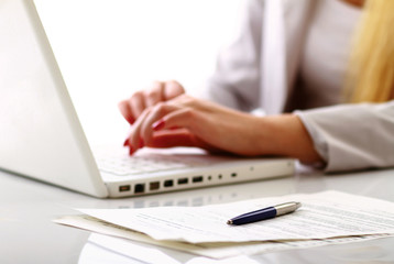 Close-up of businesswoman typing documents