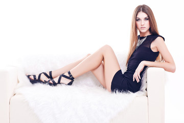 full-length portrait of beautiful brunette young woman on couch