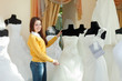 bride chooses wedding outfit in bridal boutique