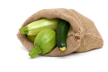 fresh marrow and zucchini in a burlap bag isolated on white back