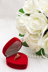 Gold ring in red box and a bouquet of roses