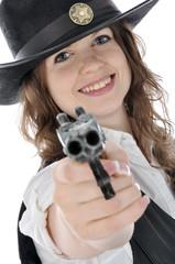 Junge Frau im Cowboy-Kostüm zielt mit Pistole