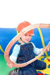 Kleiner Bauarbeiter spielt mit Schienen