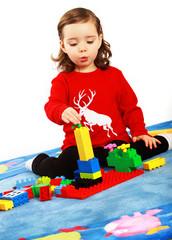 Ein Mädchen baut einen Turm mit Bausteinen
