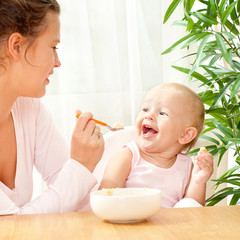 young mother feeding her baby with a spoon