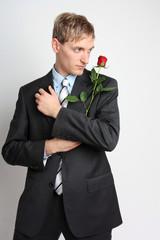 Junger Mann im Anzug mit roter Rose