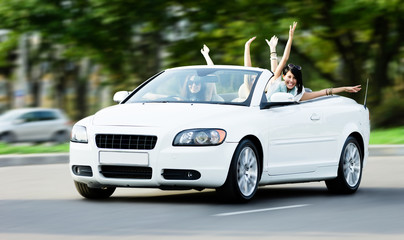 Happy girls in the white car with arms outstretched