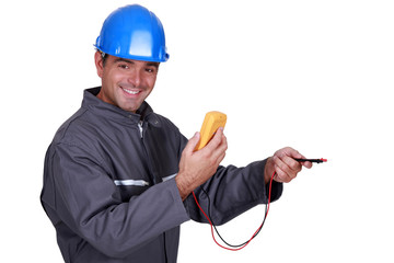 electrician holding a measurement tool and smiling