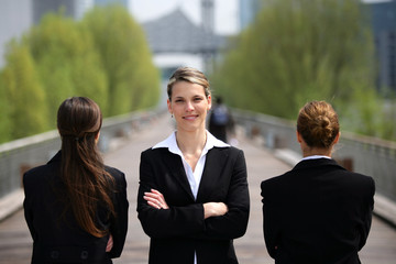 Three businesswomen stood on a bridge