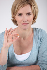 Woman holding a small orange and white capsule of medicine