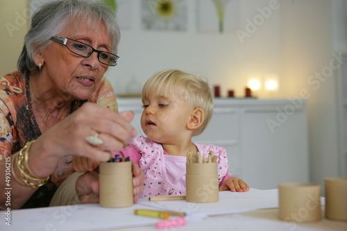 Young child coloring with grandma