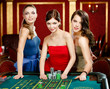 Three women place a bet playing roulette at the casino